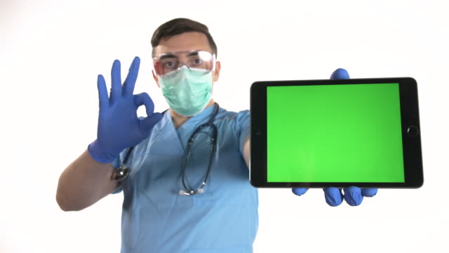医師はokサインを表示し、白い背景にクロマキーグリーンスクリーンでデジタルタブレットを保持 - 空白の画面点の映像素材/bロール