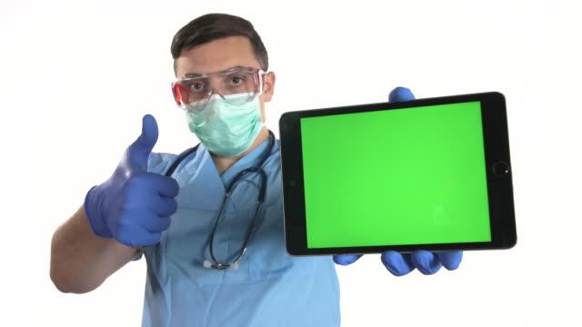 stockvideo's en b-roll-footage met de arts toont duimen omhoog teken en het houden van digitale tablet met chroma zeer belangrijk groen scherm op witte achtergrond - wit scherm