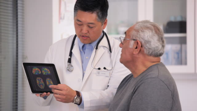 stockvideo's en b-roll-footage met ms pan doctor showing brain scan results on tablet computer to senior patient / richmond, virginia, usa - virginia amerikaanse staat