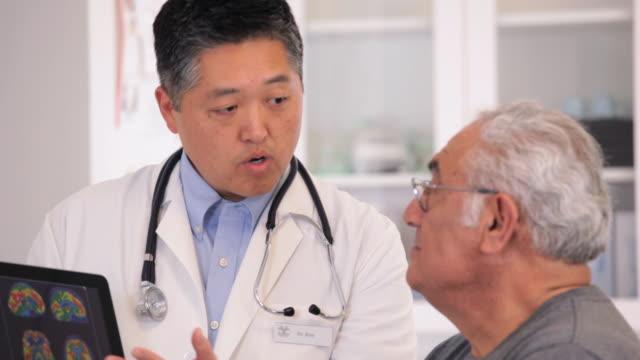 vidéos et rushes de ms tu doctor showing brain scan results on tablet computer to senior patient / richmond, virginia, usa - expliquer