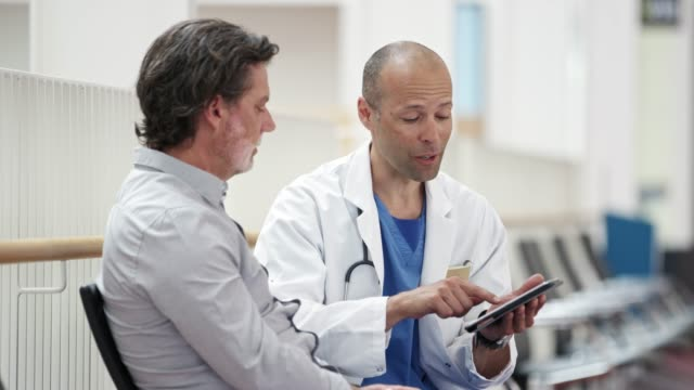 doctor showing digital tablet to male patient - mature men stock videos & royalty-free footage
