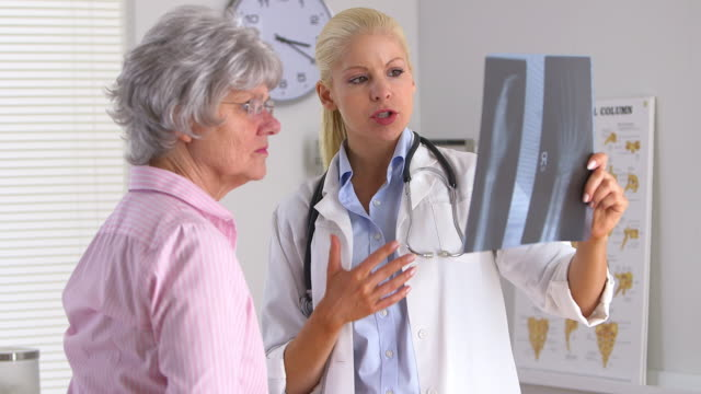 doctor showing elderly woman x ray of hand - 骨折点の映像素材/bロール