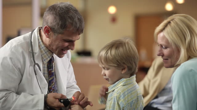 MS TU Doctor showing otoscope to boy (4-5) in waiting room / Portland, Maine, USA