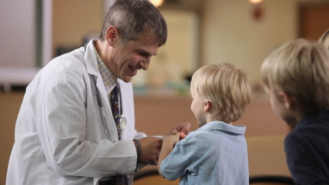MS Doctor showing otoscope to two boys (4-5, 6-7) / Portland, Maine, USA