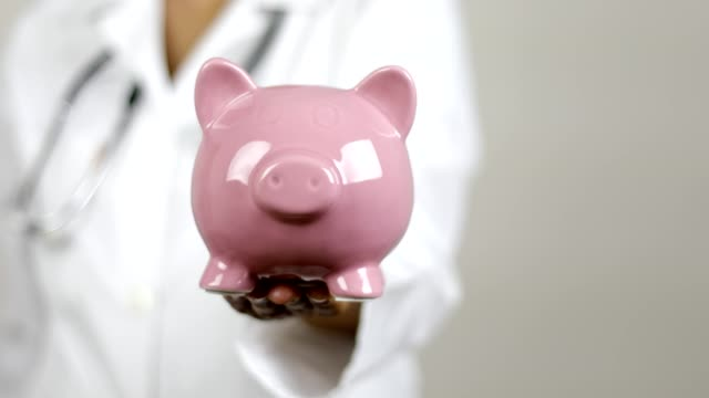 doctor showing piggy bank - expense stock videos & royalty-free footage