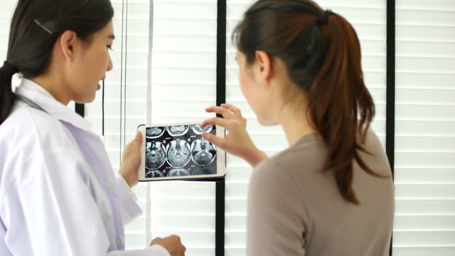 Doctor showing to her patient x-ray on digital tablet in examination room at Hospitals