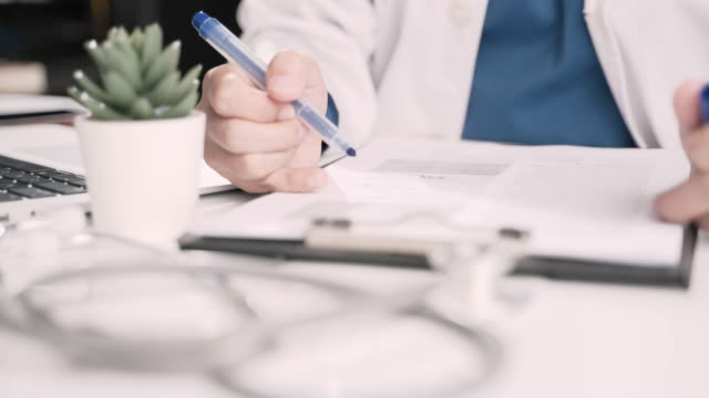 doctor signing a medical report in office - demobilisation stock videos & royalty-free footage