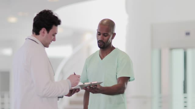doctor signing forms in hospital - permission concept stock videos & royalty-free footage
