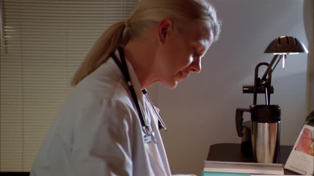 A doctor sits at her desk looking at medical charts.