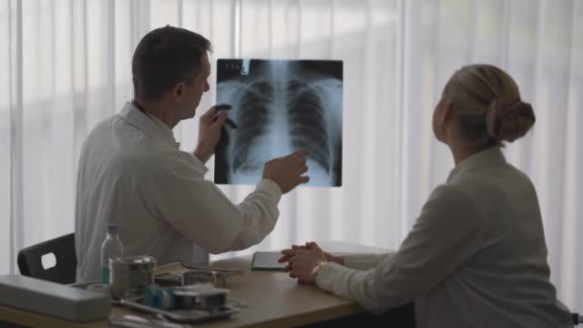 女性患者の肺の症状を説明するために机の上に座っている医師 - レントゲン点の映像素材/bロール