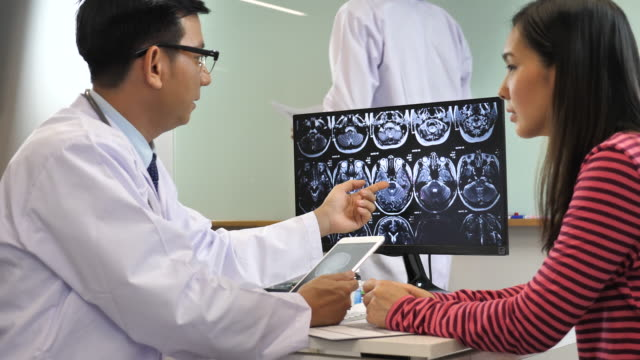vídeos de stock, filmes e b-roll de médico falando com seu paciente com imagem de raio-x do cérebro na mesa no hospital, câmera lenta - quadro médico