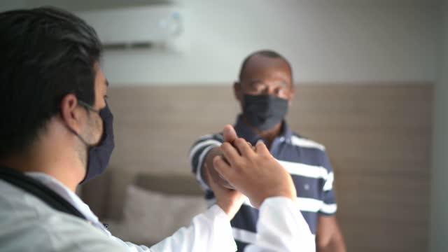 vídeos de stock, filmes e b-roll de médico esticando paciente sênior em visita domiciliar - moving image