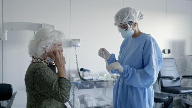 arzt nimmt coronavirus-probe von seniorin - schutzbrille stock-videos und b-roll-filmmaterial