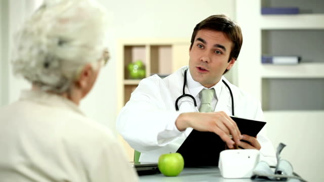 doctor taking pillsand giving a apple to patient. - over 80 stock videos and b-roll footage