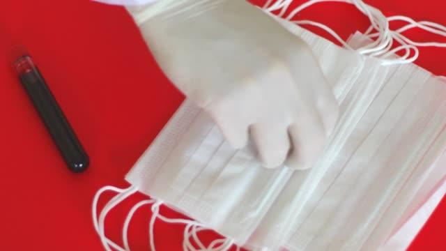 テーブルから保護マスクを取る医師 - レスピレーターマスク点の映像素材/bロール
