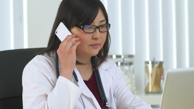 vídeos de stock e filmes b-roll de doctor talking on her smartphone - só uma mulher de idade mediana