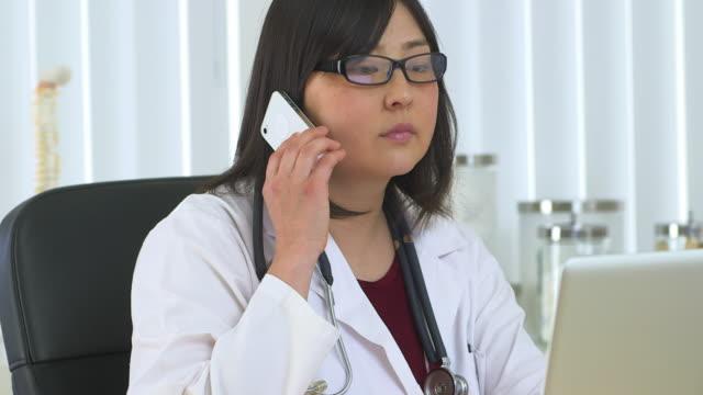 vídeos de stock e filmes b-roll de doctor talking on the phone - só uma mulher de idade mediana