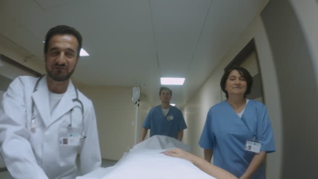 pov doctor talking to his patient while being pushed on the stretcher - stretcher stock videos & royalty-free footage