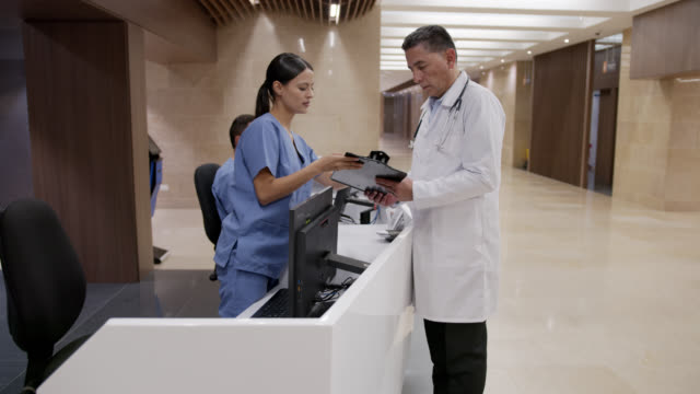 doctor talking to nurse while looking at a medical chart in the hospital's reception - secretary stock videos & royalty-free footage