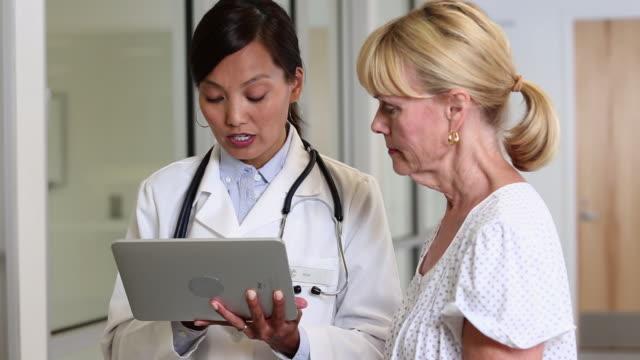 ms doctor talking to patient about test results on tablet computer / richmond, virginia, usa - kvinnlig läkare bildbanksvideor och videomaterial från bakom kulisserna