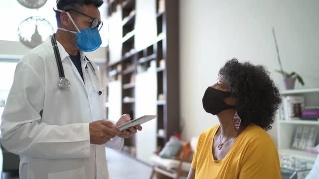 vídeos y material grabado en eventos de stock de médico hablando con paciente durante visita a casa - usando máscara facial - visita a domicilio