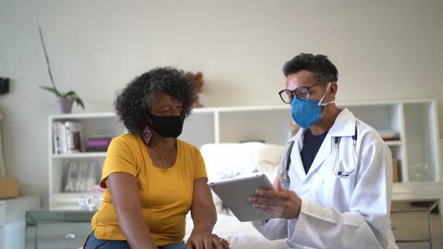 doctor talking to patient during home visit - wearing face mask - visit stock videos & royalty-free footage