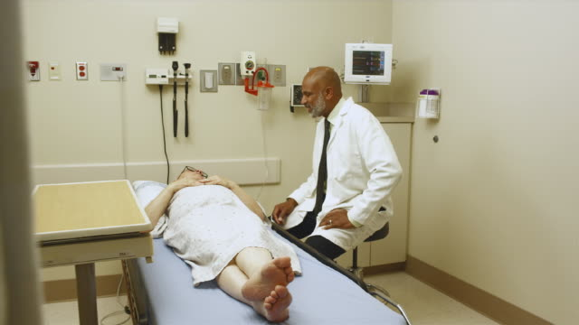 ws ds doctor talking to patient in exam room / edmonds, washington, usa - examination gown stock videos and b-roll footage