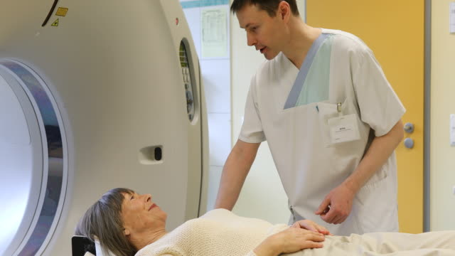 Doctor talking to patient lying on MRI scanner