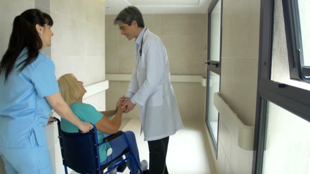 doctor talking to patient on wheelchair and nurse - pushing stock videos & royalty-free footage
