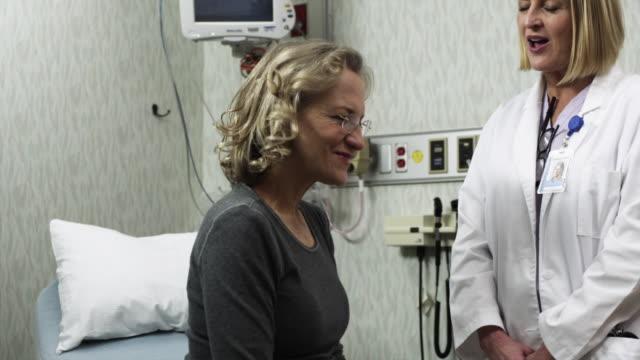ms pan doctor talking to patient / payson, utah, usa - ペイソン点の映像素材/bロール