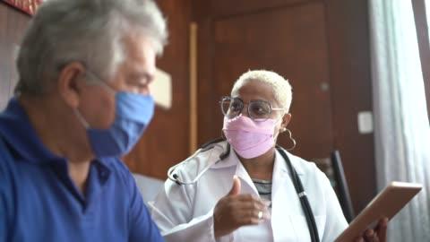 läkare talar med äldre manlig patient samtidigt som i ett hem besök - besök bildbanksvideor och videomaterial från bakom kulisserna