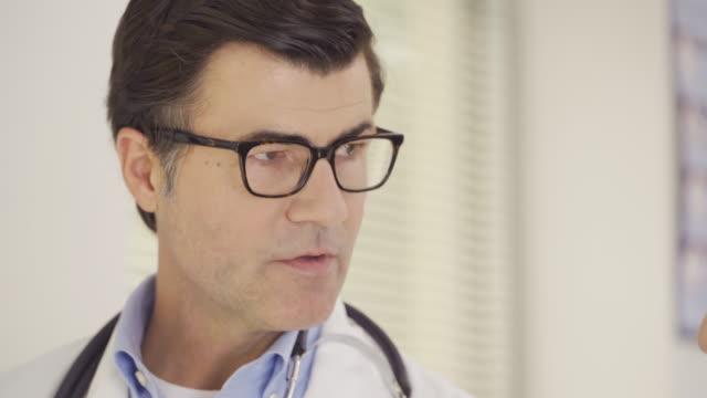 doctor talking to senior man - alterungsprozess stock-videos und b-roll-filmmaterial