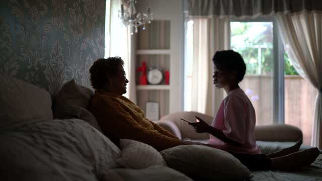 doctor talking to senior patient in the bedroom during home visit - patient stock videos & royalty-free footage