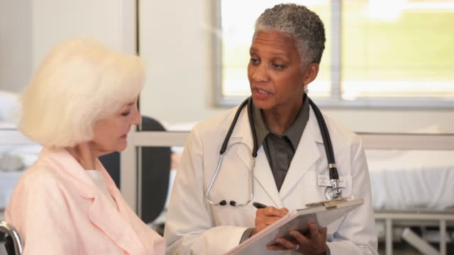 MS Doctor Talking to Senior Patient in Wheelchair, Taking Notes on Pad / Richmond, Virginia, USA