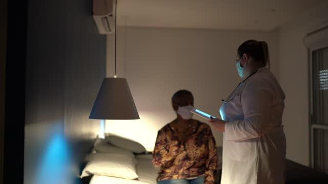 stockvideo's en b-roll-footage met arts die aan hogere vrouwenpatiënt op medisch bezoek bij haar huis spreekt - gebruikend gezichtsmasker - buiten de vs