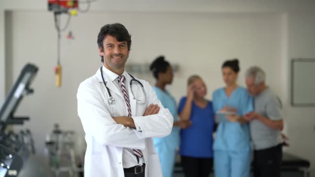 Doctor talking with a group of patients and nurses and then walking up to the camera smiling with arms crossed