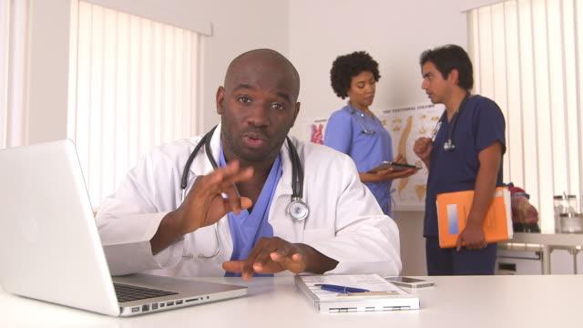 vídeos y material grabado en eventos de stock de doctor talking with colleagues in background - fiabilidad