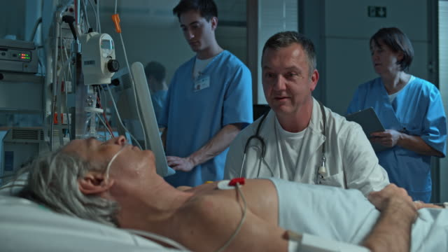 DS arts praten met zijn mannelijke patiënt in de ICU op nacht