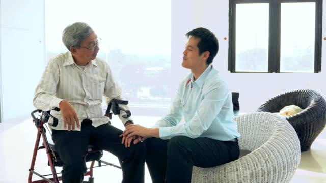 vídeos de stock, filmes e b-roll de médico falando com o paciente - cadeira de rodas equipamento ortopédico