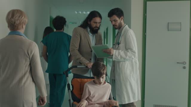 vídeos y material grabado en eventos de stock de doctor hablando con un hombre con chica en silla de ruedas - fiabilidad