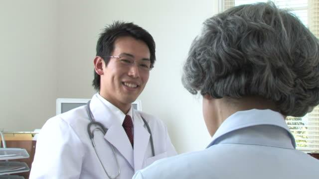 vídeos de stock e filmes b-roll de doctor talking with patient in consultation room - exame médico procedimento médico
