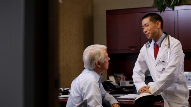 MS PAN Doctor talking with patient in doctors office / Albany, New York, United States