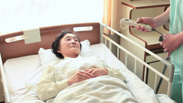 MS Doctor talking with senior woman in sick room and adjusting her bed with remot / Shibuya, Tokyo, Japan