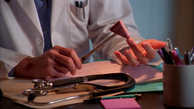 A doctor taps her fingers with a reflex hammer.