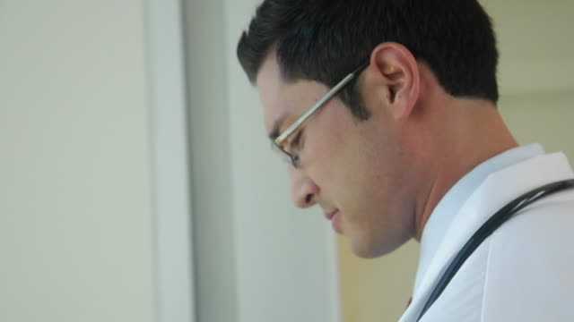 stockvideo's en b-roll-footage met cu tu doctor text messaging and smiling to colleagues, seattle, washington, usa - overhemd en stropdas