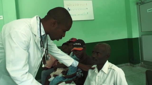 vídeos de stock e filmes b-roll de doctor treats patient at hospital ollowing devastating earthquake haiti 11 march 2010 - hispaniola