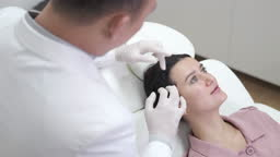 Doctor trichologist examining womans hair scalp for eczema, dermatitis, psoriasis, hair loss, dandruff or dry scalp problem