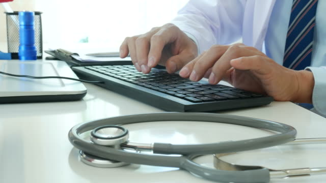 doctor typing letter, consulting patients