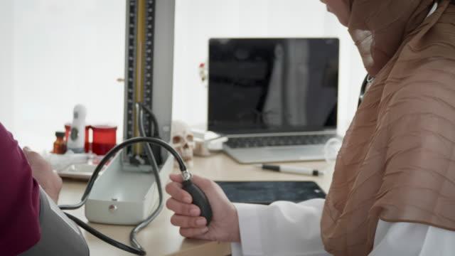 doctor using blood pressure measuring patient - blood pressure gauge stock videos & royalty-free footage