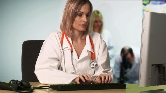 montage ms doctor using computer - 男性と複数の女性点の映像素材/bロール